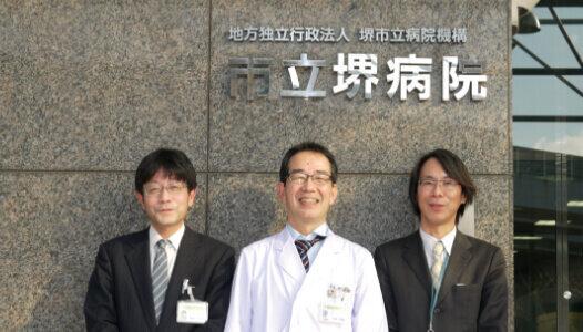 診療局長・中央手術科部長 医療情報室<br> 室長 大里 浩樹様(中央)<br> 主査 森本 昌明様(左)<br> 山根 貴久様(右)